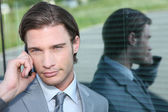 Male executive on cellphone reflected in window — Stock Photo
