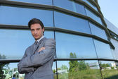 Young businessman standing in front of a building — Stockfoto