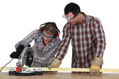 Man and woman using circular saw — Stock Photo
