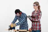 Woman supervising carpenter — Stock Photo