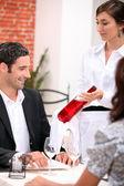 Ayundante sumiller mostrando una botella de vino a un cliente — Foto de Stock