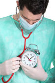 Doctor auscultating alarm clock — Stock Photo