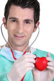 Young doctor listening to a model heart through a stethoscope — Stock Photo