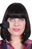 Brunette woman applying makeup — Stock Photo