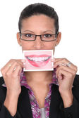 Woman holding up an enlarged picture of her mouth — Stock Photo