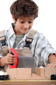 Closeup of a young boy sawing word — Stock Photo