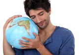 Man hugging a globe — Stock Photo