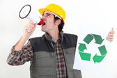 Craftsman holding a recycling label and shouting through a megaphone — Stock Photo