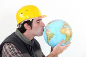 A construction worker kissing a globe. — Stock Photo