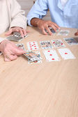 Elderly woman playing card game with young man — Stock Photo