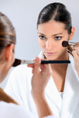 Brunette applying blusher in the mirror — Stok fotoğraf