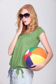 Studio shot of a cute young redhead with a beach ball — Stock Photo