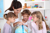 Woman and children looking at a terrestrial globe — Stock Photo