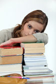 Young woman laying her head on a stack of books — Stock Photo