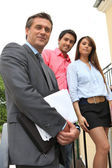 Estate agent with a young couple — Stock Photo