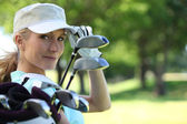 Woman with golf clubs — Stok fotoğraf
