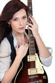 Woman with an electric guitar — Stockfoto