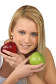 Blond woman choosing between red and green apples — Stok fotoğraf