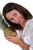 Woman listening to pineapple — Stock Photo