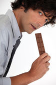 Young man with chocolate bar — Stock Photo