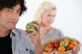 Man with apple and woman with basket in the background — Stock Photo