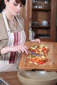 Mladá žena sběr škrabka na zeleninu — Stock fotografie