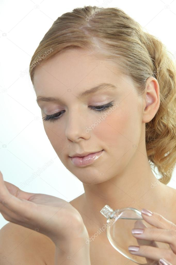 Young woman dabbing perfume onto her wrist — Stock Photo #14557225