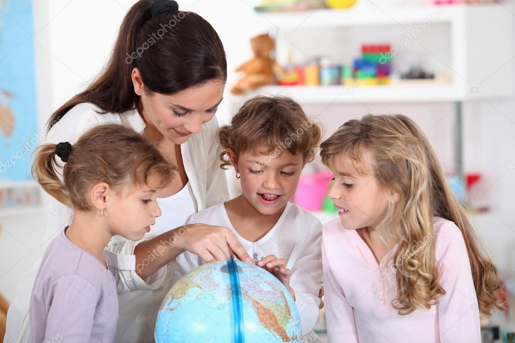 Woman and children looking at a terrestrial globe  Stock Photo #14558021