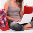 Woman sitting on sofa with computer and bags - Stock Photo