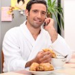 Royalty-Free Stock Photo: Young man making a call while having breakfast