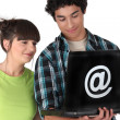 Teenage couple looking at a laptop emblazoned with an @ sign — Stock Photo