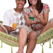 Couple enjoying tropical cocktails whilst sat on hammock — Stock Photo