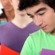 Students in a line holding folders — Stock Photo