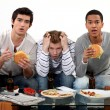 Stock Photo: Three male friends eating burgers and watching television