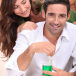 Woman surprising man with cocktail — Stock Photo