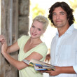 Couple looking at a tourist board - Stock Photo