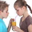 Children sharing a glass of juice — Stock Photo