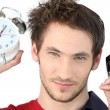 Man stood alarm clock and mobile - Stock Photo
