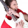 Man enthusiastically playing his guitar — Stock Photo