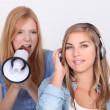 Stockfoto: Young girl oblivious to her friend yelling into megaphone