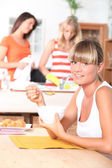 Young woman eating breakfast with friends — Stock Photo