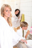 Three women in a bathroom — Stock Photo