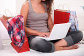 Woman sitting on sofa with computer and bags — Stock Photo