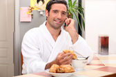 Young man making a call while having breakfast — Stock Photo