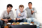 Young men watching a football game — Stock Photo