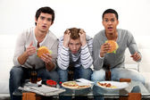 Three male friends eating burgers and watching television — Stock Photo