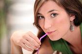 Primer plano de una joven mujer chupando una pajita rosa — Foto de Stock