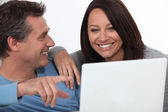 Couple laughing whilst looking at laptop screen — Stock Photo