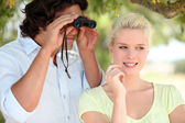 Couple outdoors with a pair of binoculars — Stock Photo