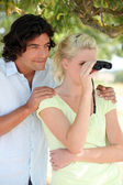Couple using pair of binoculars — Stock Photo
